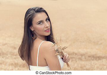Young woman resting in a wheat field on a sunny day