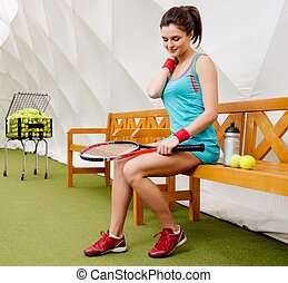 Young woman resting on a bench after tennis workout