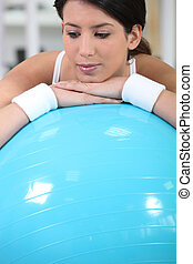 Young woman resting on a gym ball