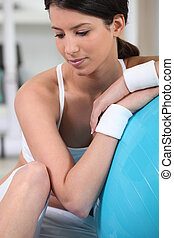 Young woman resting on an exercise ball