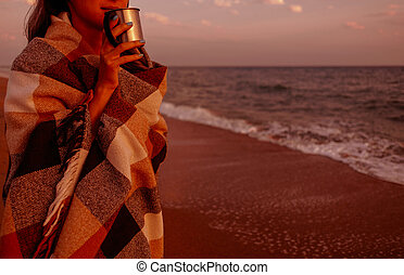 Young woman resting on beach at sunset.