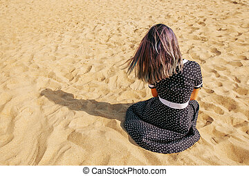 Young woman resting on sand.