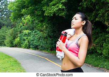 Young woman resting with towel and water bottle after running