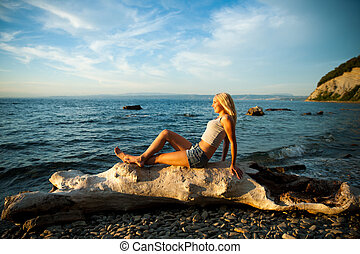 Young woman rests on the beach on a hot summer day