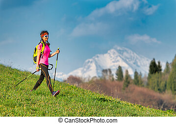 Young woman returning from a Nordic walking excursion in the mountains in spring