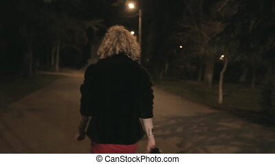 Young woman returns home through the dark park, begins to...