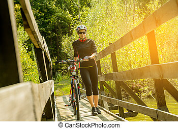 Young woman riding a bicycle in a bridge at sunset.