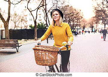 Young woman riding a bicycle in sunny spring town.