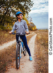 Young woman riding a bicycle in the field