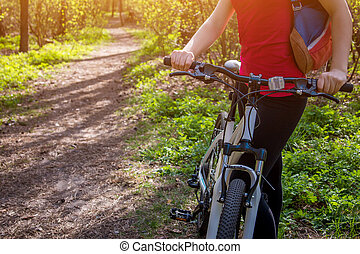 Young woman riding a bicycle in the forest