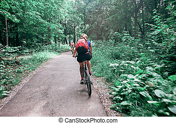 Young woman riding a bicycle in the park in motion, rear view