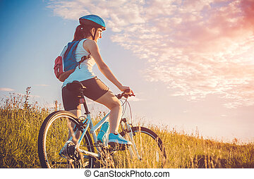 Young woman riding a bicycle on the field