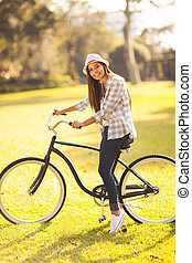 young woman riding a bicycle outdoors