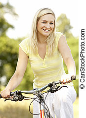 Young woman riding bike in countryside