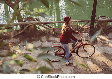 Young woman riding bike on fall day from top angle - High...