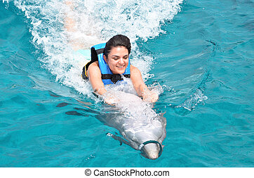 young woman riding dolphin