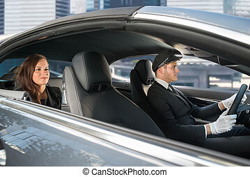 Young Woman Riding In A Car With Chauffeur