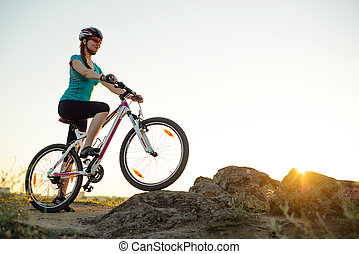 Young Woman Riding Mountain Bike on the Summer Rocky Trail at Beautiful Sunset. Travel, Sports and Adventure Concept.