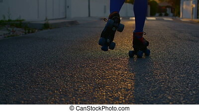 Young Woman Riding on Roller Skates on the Street at Sunset....