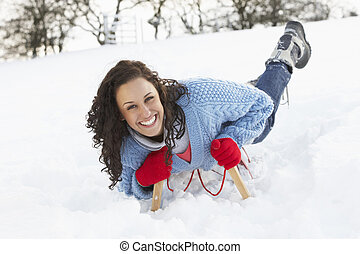 Young Woman Riding On Sledge In Snowy Landscape