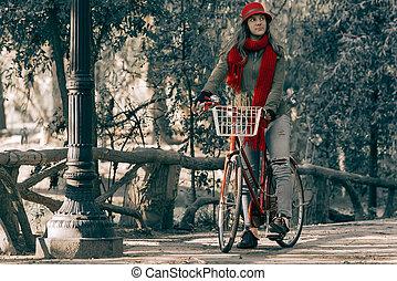 Young woman riding red vintage bike on fall season