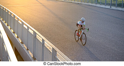 Young Woman Riding Road Bicycle on the Bridge in the City at Sunset. Healthy Lifestyle and Sport Concept.