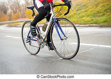 Young Woman Riding Road Bicycle on the Highway in the Cold Autumn Day. Healthy Lifestyle.