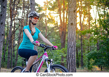 Young Woman Riding the Bike on the Trail in Beautiful Fairy Pine Forest. Adventure and Travel Concept.