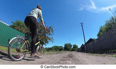 Young Woman Riding Vintage Bicycle along a Rural Road in a Village