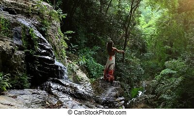 Young woman rises hands at waterfall in jungle Koh Samui. ...