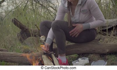 Young woman roasting marshmallows on a fire in the forest...