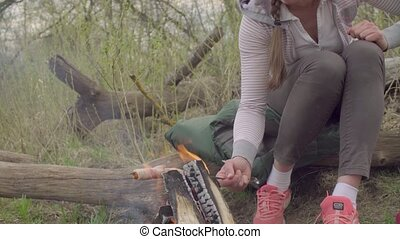Young woman roasting sausage on a fire - Close up hand of...