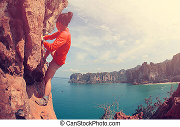 young woman rock climber climbing at seaside mountain cliff...