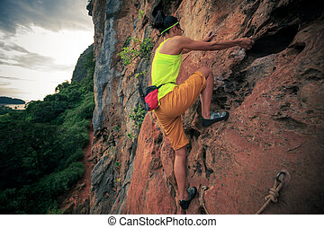 young woman rock climber climbing on cliff