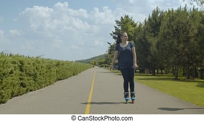 Happy female roller with ponytail from afro-braids rollerblading along public park lane. Positive carefree woman enjoying freedom of active summer leisure while riding roller blades outdoors.