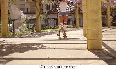 Young Woman Roller Skating on Sunny Promenade - Full Length...