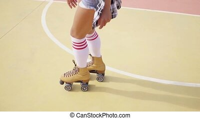 Young woman roller skating outdoors - Close up high angle...