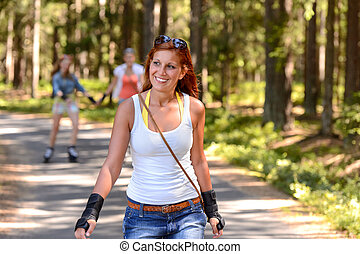 Young woman roller skating outdoors summer sport on...
