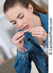 young woman rolling cigarette