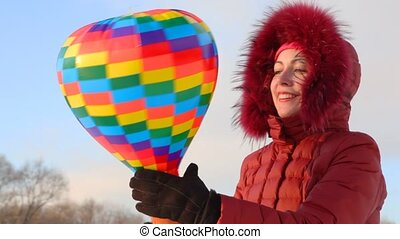 young woman rotating balloon in hands, winter