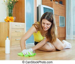 young woman rubbing wooden floor