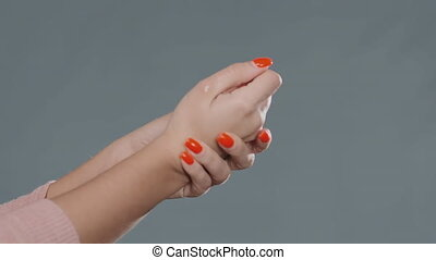 young woman rubs hands with red manicure disinfecting