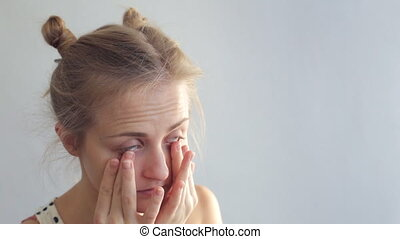 Young woman rubs her eyes. Caucasian woman rubbing eyes