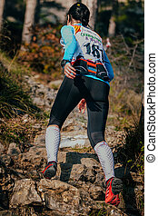 young woman runner going uphill on mountain trail. on her...