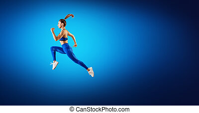 Young woman runner in blue sportwear jump in the air.