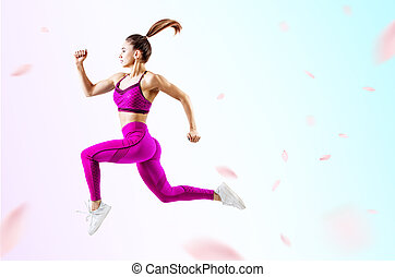 Young woman runner in purple sportswear jump in the air.
