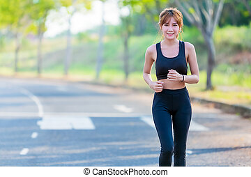 Young woman runner running on city road.