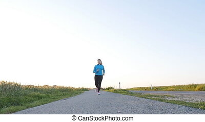 Young woman runner running on sunrise road. Fitness concept