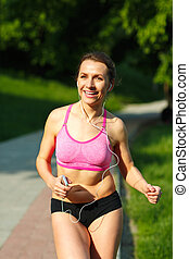 Young woman runner running on trail in the morning