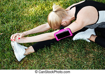 Young woman runner stretching legs outdoor